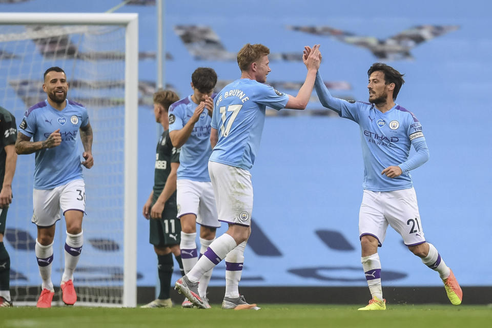Manchester City's David Silva, right , celebrates after scoring a goal during the English Premier League soccer match between Manchester City and Newcastle at the Ethiad Stadium in Manchester, England, Wednesday, July 8, 2020. (Michael Regan/Pool via AP)