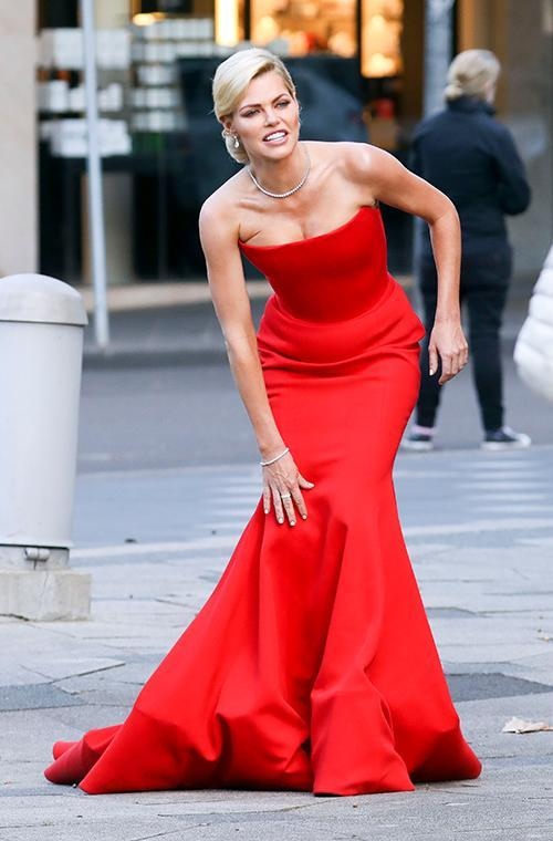 The 37-year-old turned heads as she stunned in a racy red number, however she seemed to feel the icy winter's day as she was seen hugging a hot water bottle during breaks.