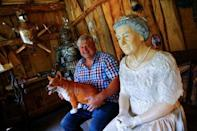"""Gary Blackburn, a 53-year-old tree surgeon from Lincolnshire, Britain, poses with a life-size model of Queen Elizabeth and a corgi dog mock-up at """"Robin Hood's hut"""" of his British curiosities collection called """"Little Britain"""" in Linz-Kretzhaus, south of Germany's former capital Bonn, Germany, August 24, 2017. REUTERS/Wolfgang Rattay"""