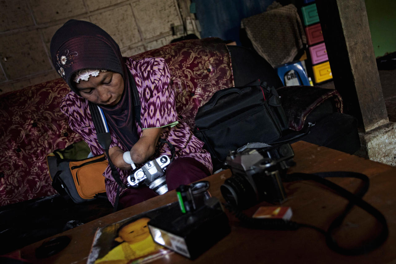 Armless professional photographer Rusidah, 44, carries out camera maintenance on March 13, 2012 in Purworejo, Indonesia. (Photo by Ulet Ifansasti/Getty Images)