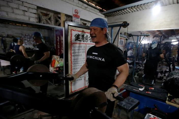 Liu Hongtao, 53, works out at a gym which has been turned from a bicycle shed inside a residential compound in the southwest of Beijing