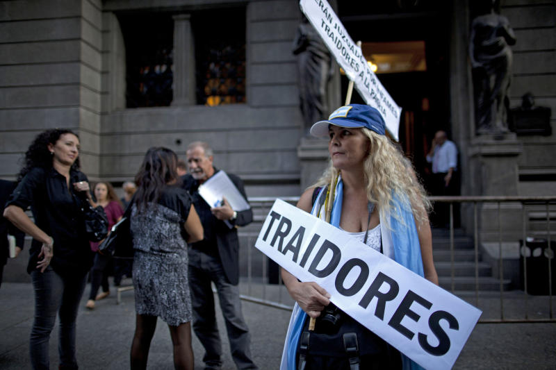 "A woman holds a banner reading in Spanish; ""Traitors,"" during a protest against comprehensive judicial reform proposed by President Cristina Fernandez outside the National Congress in Buenos Aires, Argentina, Wednesday, April 24, 2013. Lawmakers began debating major changes to the country's justice system Wednesday. Some of the changes would end indefinite injunctions against government actions, expand and popularly elect most of the magistrate's council and require executive, legislative and judicial authorities to publish their tax declarations online. (AP Photo/Natacha Pisarenko)"