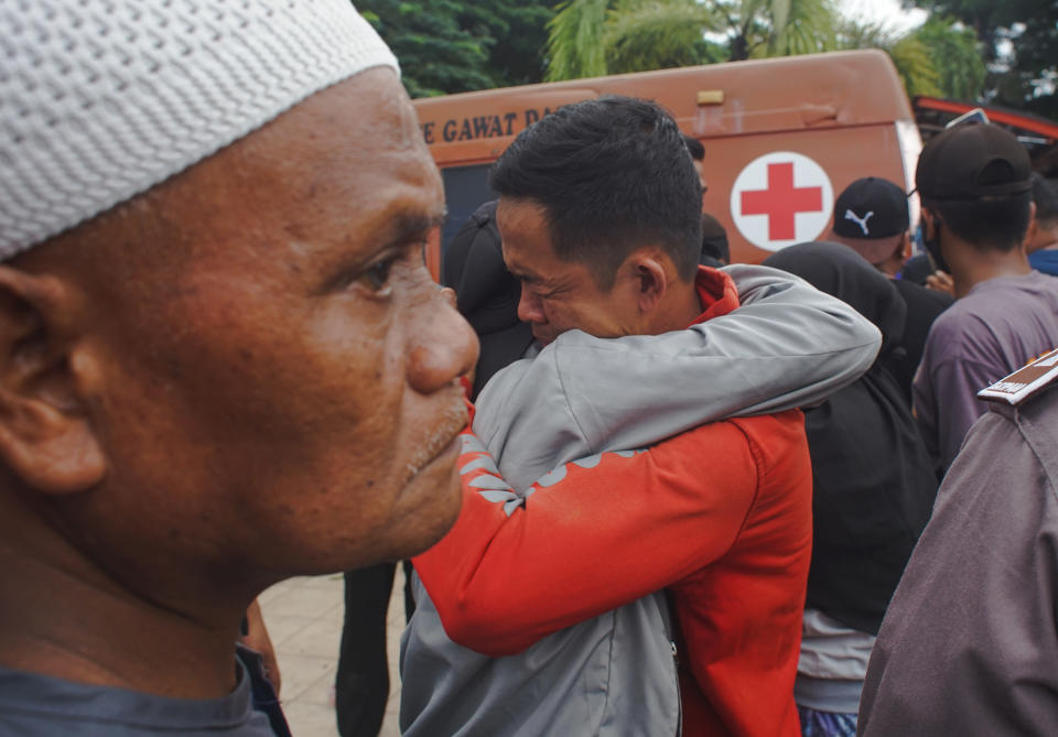 Indonesian men comfort each other following an earthquake in Mamuju, West Sulawesi, Indonesia, Friday, Jan. 15, 2021. A strong, shallow earthquake shook Indonesia's Sulawesi island just after midnight Friday, toppling homes and buildings, triggering landslides and killing a number of people. (AP Photo/Azhari Surahman)