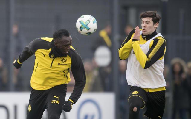 Jamaica's former sprinter Usain Bolt, left, heads the ball towards Dortmund's Tim Sechelmann, U19 team, during a practice session of the Borussia Dortmund soccer squad in Dortmund, Germany, Friday, March 23, 2018. (Bernd Thissen/dpa via AP)