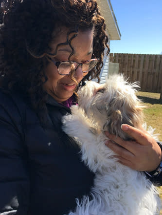 "In a photo provided by Candace Croney, Croney holds her dog, Desi, in April 2019, in Indiana. ""If we think how much time most of our pets prior to the pandemic typically would spend without people around to 24 hours a day, seven days a week, it's quite a lot,"" says Croney, a Purdue University professor who teaches about animal behavior. (Courtesy of Candace Croney via AP)"