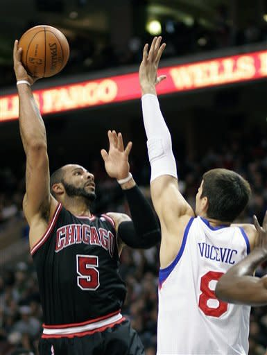 Chicago Bulls' Carlos Boozer, left, shoots over Philadelphia 76ers' Nikola Vucevic during the first half of an NBA basketball game, Sunday, March 4, 2012, in Philadelphia. (AP Photo/Tom Mihalek)