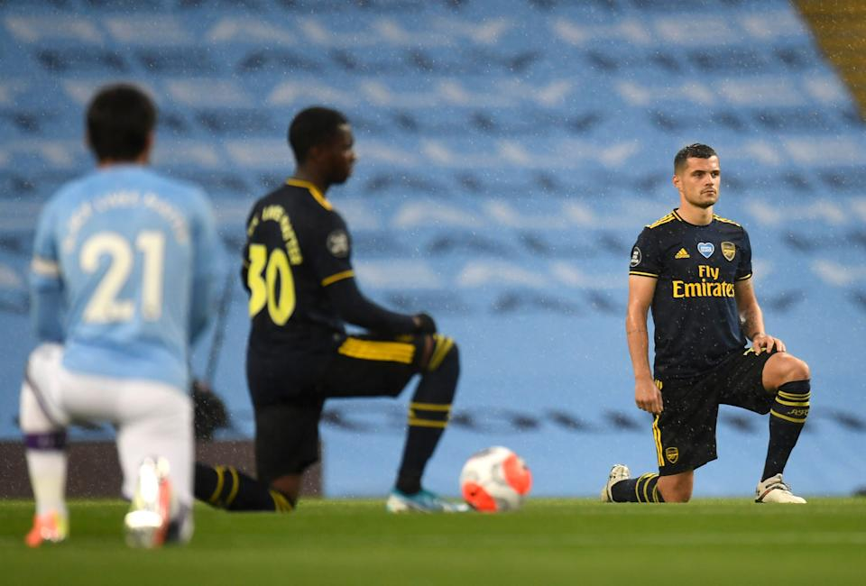 <strong>Granit Xhaka of Arsenal takes a knee in support of the Black Lives Matter movement prior to the Premier League match between Manchester City and Arsenal.</strong> (Photo: Pool via Getty Images)