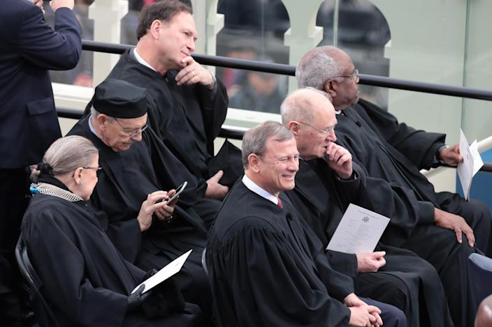 <p>Supreme Court Justices (from L) Ruth Bader Ginsburg, Stephen Breyerm Samuel Alito, John Roberts, Anthony Kennedy, and Clarence Thomas sit on the West Front of the U.S. Capitol on January 20, 2017 in Washington, DC. (Photo: Scott Olson/Getty Images) </p>