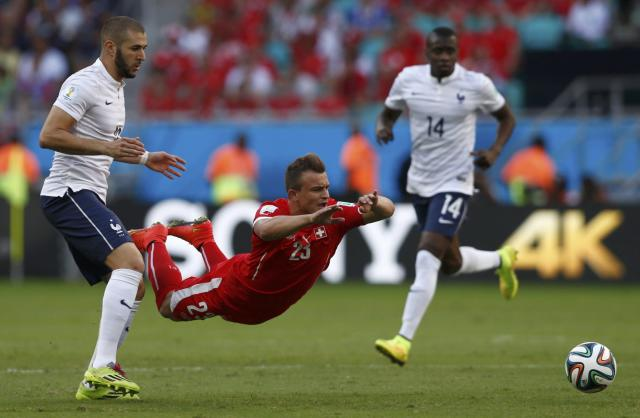 France's Karim Benzema (L) watches as Switzerland's Xherdan Shaqiri falls to the ground in front of him as they fight for the ball during their 2014 World Cup Group E soccer match at the Fonte Nova arena in Salvador June 20, 2014. REUTERS/Marcos Brindicci (BRAZIL - Tags: SOCCER SPORT WORLD CUP TPX IMAGES OF THE DAY)