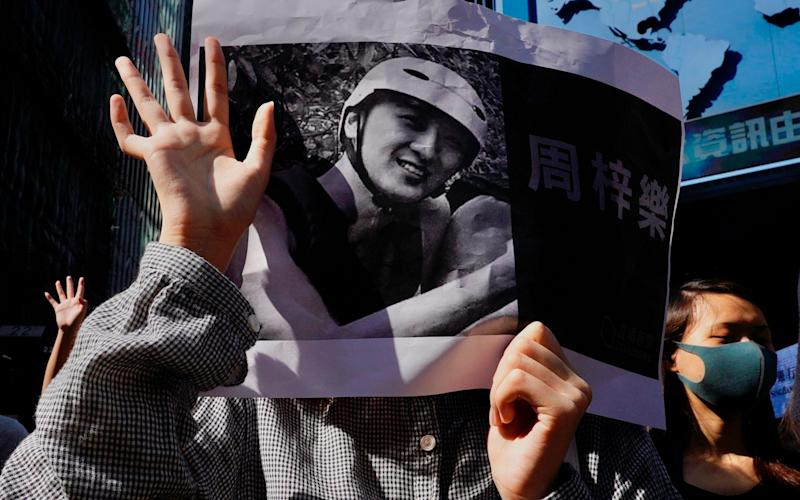 Protesters hold a photo of Chow Tsz-Lok during a memorial flash mob to remember him in Hong Kong - AP
