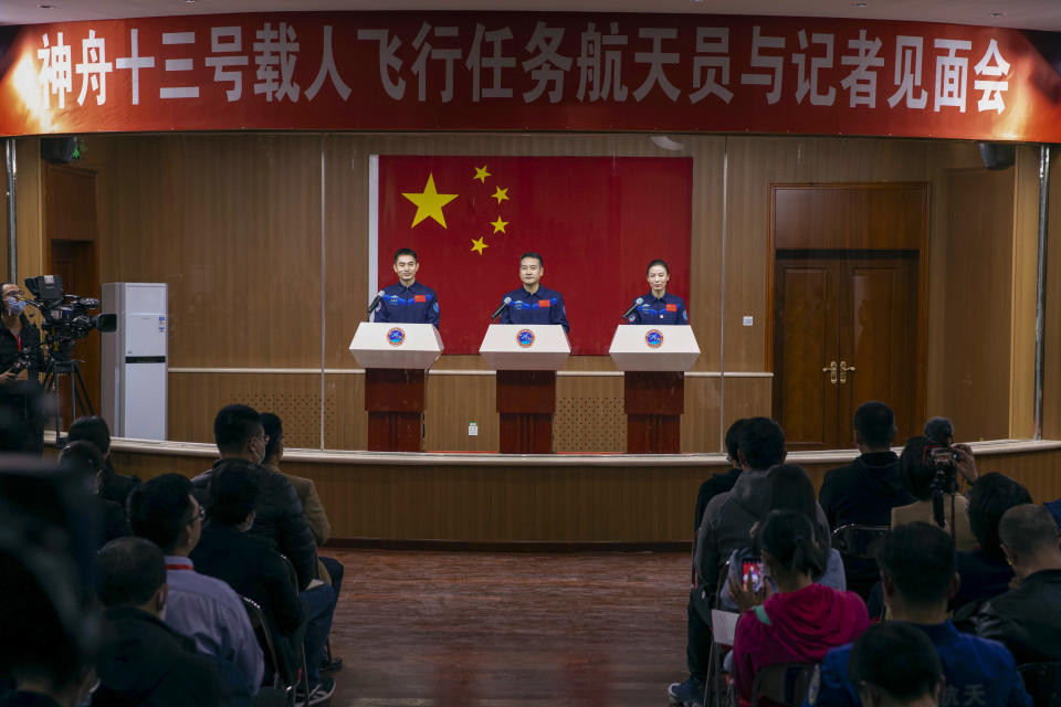In this photo released by Xinhua News Agency, Chinese astronauts, from left, Ye Guangfu, Zhai Zhigang and Wang Yaping meet the reporters at a press conference at the Jiuquan Satellite Launch Center ahead of the Shenzhou-13 launch mission from Jiuquan in northwestern China, Thursday, Oct. 14, 2021. China is preparing to send three astronauts to live on its space station for six months — a new milestone for a program that has advanced rapidly in recent years. (Ju Zhenhua/Xinhua via AP)
