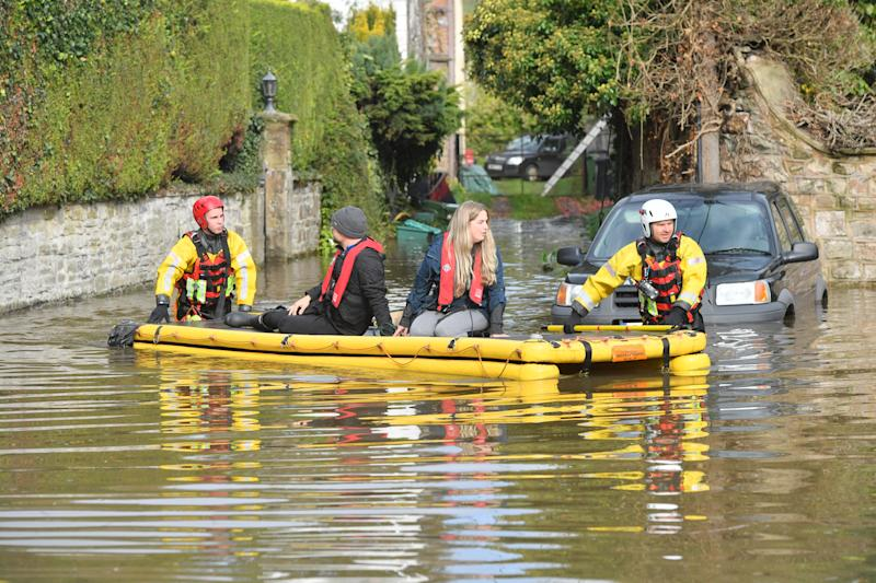 Members of Gloucestershire Fire & Rescue Service rescue residents stranded in flood water from the River Wye in Lower Lydbrook, Gloucestershire.