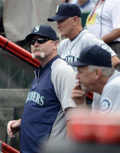 Seattle Mariners manager Eric Wedge, left, watches from the dugout during a baseball game against the Cincinnati Reds at Great American Ball Park in Cincinnati, Saturday, July 6, 2013. (AP Photo/Michael E. Keating)