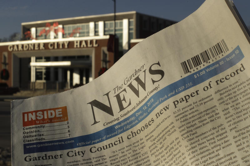 The Gardner News, with a front-page story on it's loosing status of the city's paper of record, is seen with the Gardner City Hall in the distance Friday, Dec. 20, 2019, in Gardner, Kan. The City Council voted to move legal ads to another publication in a nearby city as a cost-saving move only weeks after the city's mayor and a council member accused the paper of publishing inaccurate material. (AP Photo/Charlie Riedel)