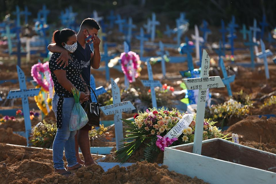 TOPSHOT - Relatives mourn during the funeral of COVID-19 victim Maria Estela Maris Melo, at the Nossa Senhora Aparecida cemetery in Manaus, Amazonas state, Brazil, on December 30, 2020. - Latin America and the Caribbean on Tuesday became the second region after Europe to top half a million deaths from Covid-19, according to an AFP count based on official tallies. There have been at least 500,800 deaths among the 29 countries in the region, with more than half of those in Brazil. (Photo by Michael DANTAS / AFP) (Photo by MICHAEL DANTAS/AFP via Getty Images)