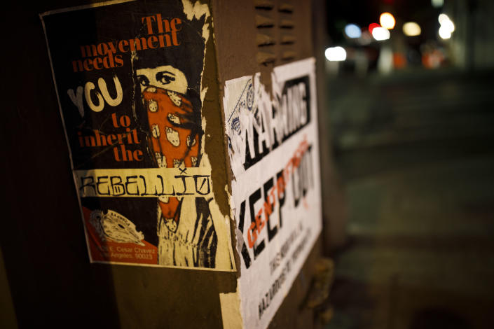 """Posters on a Boyle Heights, Los Angeles, utility box state, """"The Movement Needs You To Inherit The Rebellion"""" and """"Warning – Gentrifiers Keep Out – This Hood Will Be Hazardous to Your Health."""" (Photo: Patrick T. Fallon for Yahoo News)"""