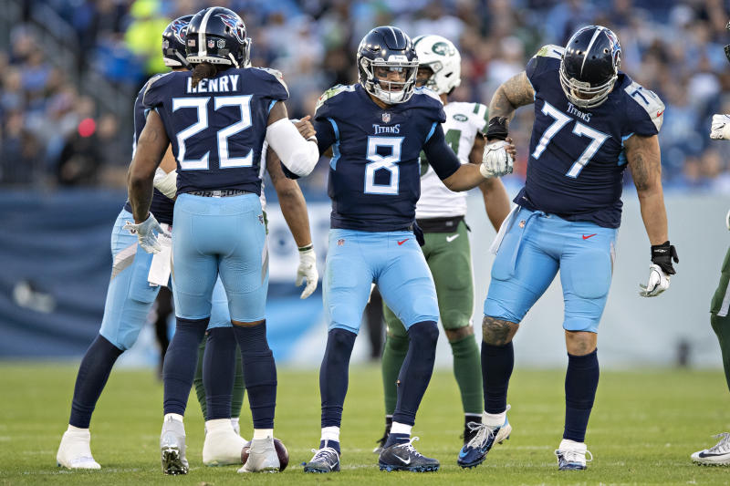 Marcus Mariota #8 is helped up by Taylor Lewan #77 and Derrick Henry #22 of the Tennessee Titans