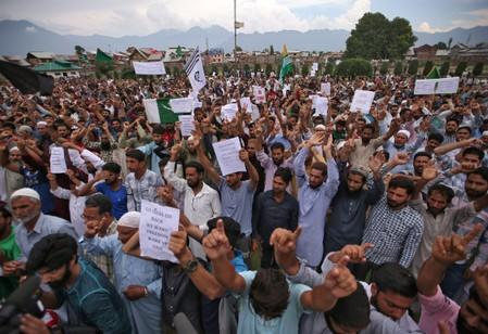 Kashmiris hold placards as they shout slogans at a protest in Srinagar