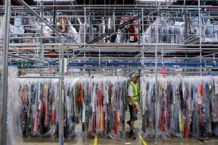 """A person moves through clothing in the storage area at Rent the Runway's """"Dream Fulfillment Center"""" in Secaucus, New Jersey"""