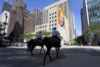 Chicago mounted police officers patrol Chicago's Magnificent Mile with an Andy Warhol mural of Marilyn Monroe in the background, on Tuesday, Aug. 11, 2019. (AP Photo/Charles Rex Arbogast)
