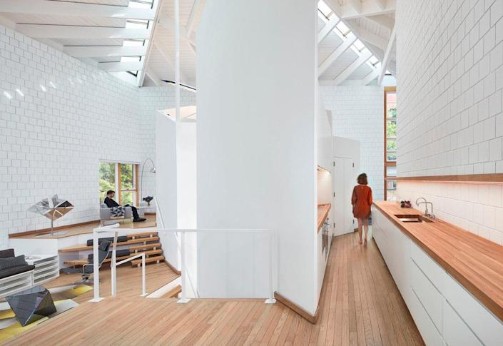 A long kitchen counter in Walter Netsch's SOM-Renovated Chicago home runs parallel to an elevated office/living area level.