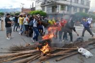 People carry a log of wood to build a barricade during a protest against what they say was police brutality exerted in recent protests against President Ivan Duque's government's tax reform in Cali