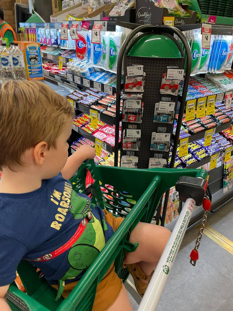 Child in trolley inside Woolworths next to button batteries.