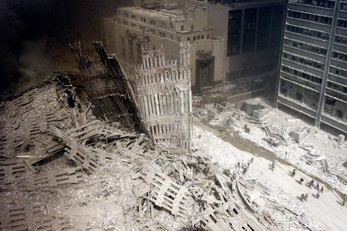 """Lilliputian figures -- firefighters stark against the grayish white dust that blanketed so much of lower Manhattan -- walk a path cleared of rubble near the base of the destroyed south tower in the days after the attacks. Aside from the still-staggering scale of the destruction, however, what truly astonishes in Peter Morgan's picture is the suggestion -- as one senses amid Roman ruins, for example, or in ash-entombed figures from Pompey -- of an entire civilization's wreckage. There is an ancient feel to the photograph that sparks a lingering question: Is this the literal end of the figurative """"American Century""""? <br><br>(Photo: PETER MORGAN/Reuters /Landov )<br><br>For the full photo collection, go to <a href=""""http://www.life.com/gallery/59971/911-the-25-most-powerful-photos#index/0"""" rel=""""nofollow noopener"""" target=""""_blank"""" data-ylk=""""slk:LIFE.com"""" class=""""link rapid-noclick-resp"""">LIFE.com</a>"""