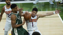 Milwaukee Bucks forward Giannis Antetokounmpo (34) and Phoenix Suns guard Devin Booker (1) battle for a loose ball during the second half of Game 3 of basketball's NBA Finals in Milwaukee, Sunday, July 11, 2021. (AP Photo/Paul Sancya)