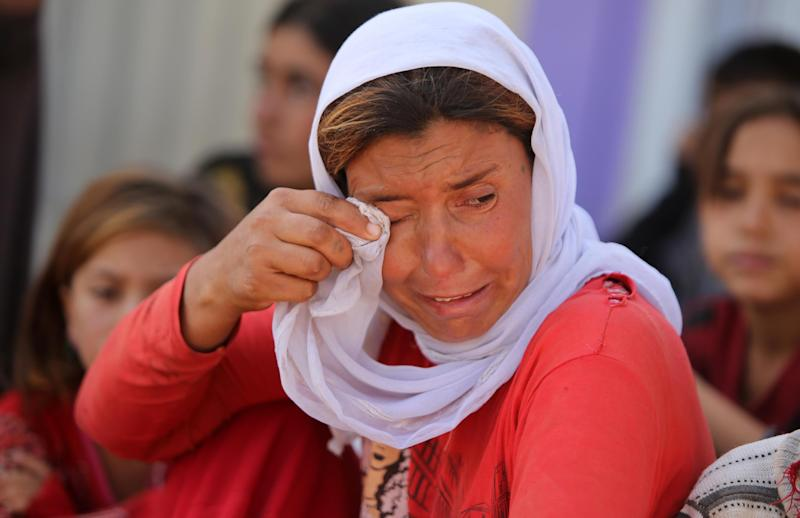 A displaced Iraqi Yazidi woman wipes her eyes at the Bajid Kandala camp near the Tigris River, in Kurdistan's western Dohuk province, where they took refuge after fleeing advances by Islamic State jihadists in Iraq on August 13, 2014 (AFP Photo/Ahmad al-Rubaye)