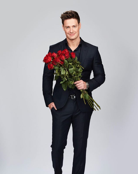 A photo of The Bachelor Australia's Matt Agnew wearing a suit and holding a large bunch of red roses