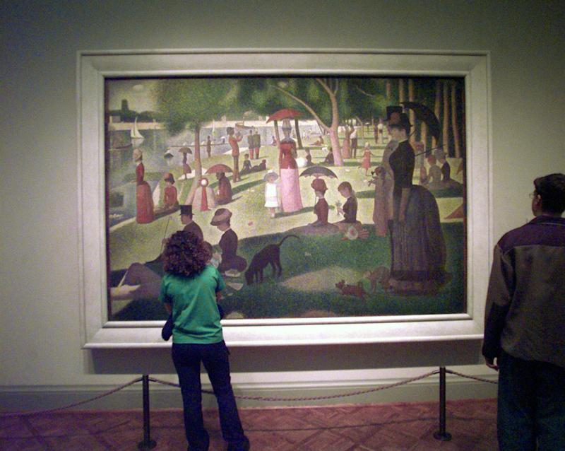 "A patron takes in ""A Sunday on La Grande Jatte-1884"" by French Post Impressionist artist Georges Seurat at the Art Institute of Chicago, Oct. 30, 1998. The museum received two conti-crayon drawings by Seurat that were done as a figure study for his famous painting. The drawings came from the Museum of Modern Art in New York which had to give away four impressionist artworks valued at more than $40 million because the patron who bequeathed them at her death in 1948 believed they would no longer be ""modern"" after 50 years. (AP Photo/Charles Bennett)"