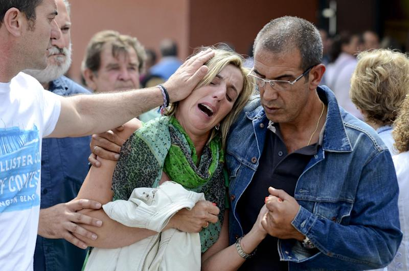 Relatives of victims involved in a train accident react at a victims information point in Santiago de Compostela, Spain, on Thursday July 25, 2013. Relatives of victims from a train crash in northwestern Spain sobbed and hugged each other Thursday near a makeshift morgue in a sports arena for the victims as the death toll rose to 78 and investigators tried to determine the cause. The train jumped the tracks and at least one passenger told a radio station that it appeared to be going very fast as it went into a pronounced curve while approaching the station in this Catholic shrine city on the eve of a major religious festival. (AP Photo/Brais Lorenzo)