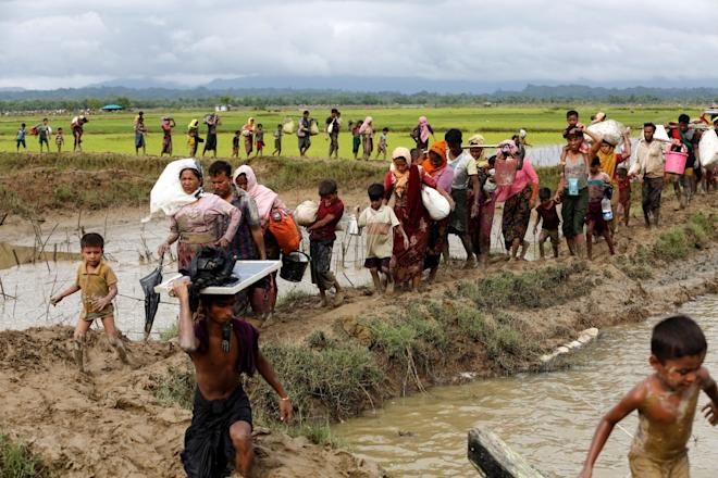 A group of Rohingya refugee people walk towards Bangladesh after crossing the Bangladesh-Myanmar border in Teknaf, Bangladesh.