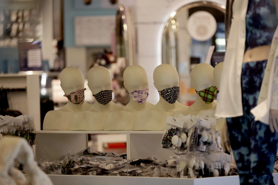 Mannequin heads are seen through the front window displaying face masks inside the temporarily closed Topshop flagship store on Oxford Street, during England's second coronavirus lockdown, in London, Monday, Nov. 30, 2020. Arcadia Group, the retail empire of tycoon Philip Green, which owns well-known British fashion chains like Topshop and employs around 15,000 people, appears to be on the brink of collapse following the economic shock of the coronavirus pandemic. (AP Photo/Matt Dunham)