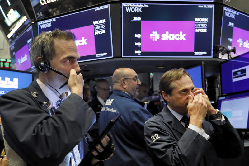 Traders Gregory Rowe, left, and Dudley Devine, right, talk into their mobile phones on the floor of the New York Stock Exchange as they wait for the Slack Technologies IPO to begin trading, Thursday, June 20, 2019. (AP Photo/Richard Drew)