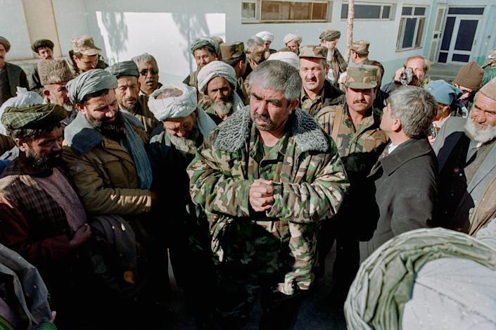 A commander addresses soldiers who stand around him.