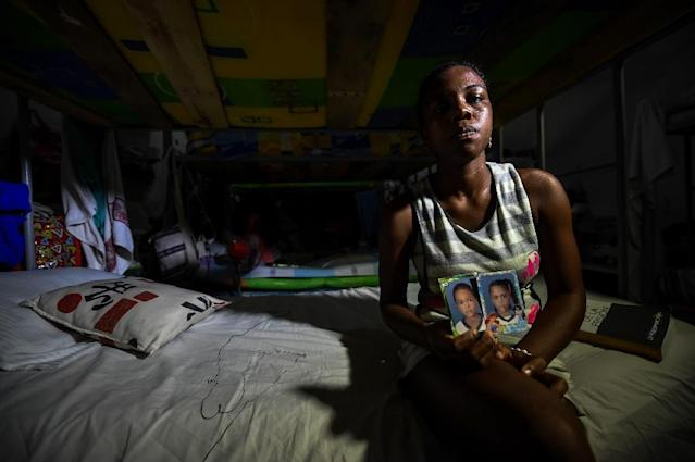 Colombian inmate Arleth Martinez shows photos of her twins in the San Diego jail in Cartagena, Colombia (AFP Photo/Raul Arboleda)