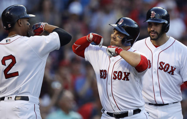 Boston Red Sox's Steve Pearce, center, is congratulated by Xander Bogaerts after his two-run home run off Texas Rangers starting pitcher Mike Minor during the first inning of a baseball game against the Boston Red Sox at Fenway Park in Boston, Monday, July 9, 2018. Red Sox's J.D. Martinez, right, looks on. (AP Photo/Charles Krupa)
