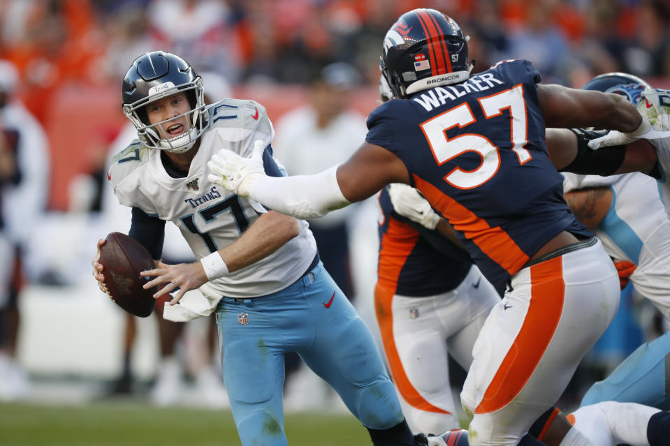 Tennessee Titans quarterback Ryan Tannehill looks to throw a pass under pressure from Denver Broncos defensive end DeMarcus Walker (57) during the second half of an NFL football game Sunday, Oct. 13, 2019, in Denver. (AP Photo/David Zalubowski)
