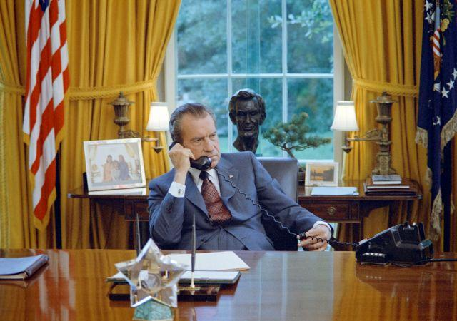 President Richard Nixon seated at his desk in the White House Oval Office