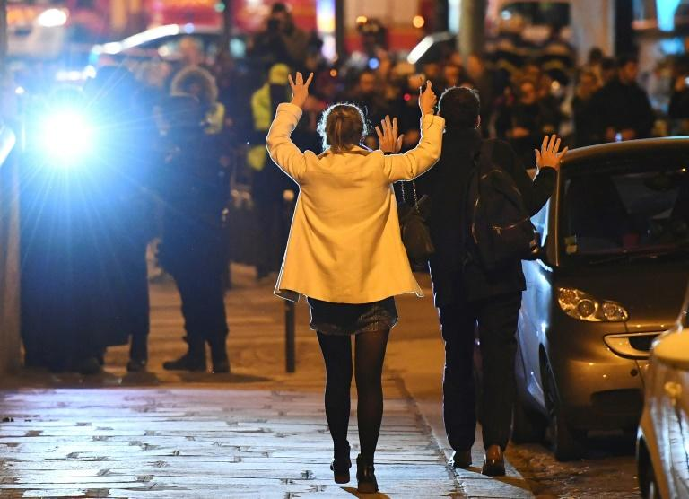 People hold their hands up as they walk towards police near the site of a shooting at the Champs Elysees in Paris