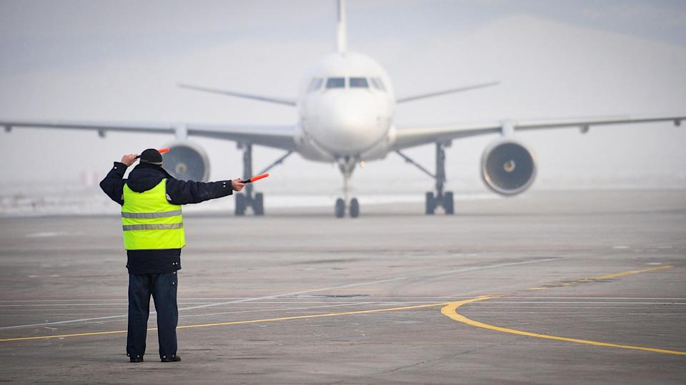 22 Industries That Pay Less (and More) Than They Did 10 Years Ag, airport worker signaling, traffic control