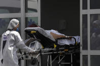 A healthcare worker pushes a patient suspected of having COVID-19 from an ambulance into the HRAN public hospital in Brasilia, Brazil, Wednesday, April 14, 2021. (AP Photo/Eraldo Peres)
