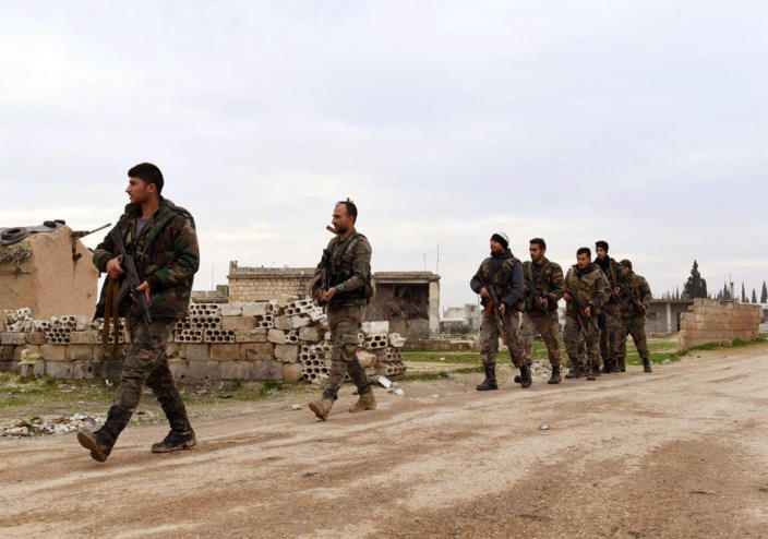 In this photo released Wednesday Feb. 5, 2020 by the Syrian official news agency SANA, shows Syrian government forces patrolling the village of Tel-Toukan, in Idlib province, northwest Syria. On Thursday, State media and opposition activists said Turkey has sent more reinforcements into northwestern Syria, setting up new positions in an attempt to stop a government offensive on the last rebel stronghold in the war-torn country. (SANA via AP)