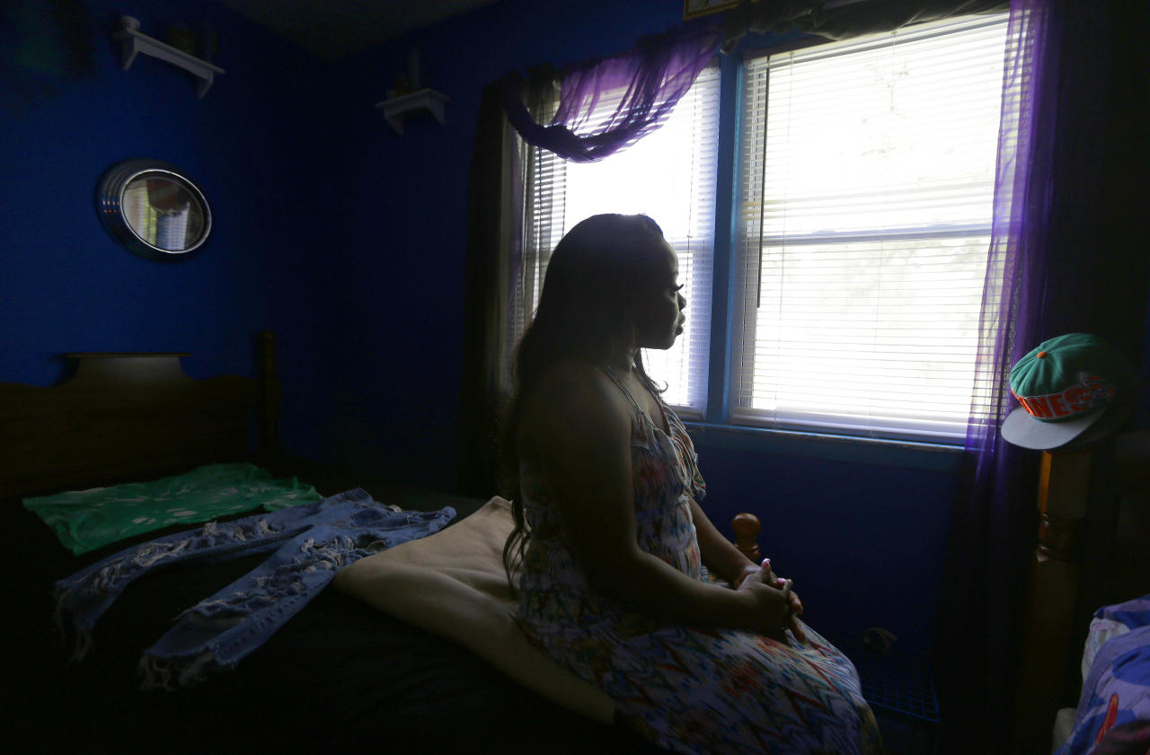 In this July 8, 2014, Felicia Jordan sits on the edge of her deceased son Ravon's bed in Fayetteville, N.C. Ravon spoke out against gun violence at a city council meeting after his best friend, Shaniqua Simmons, and her boyfriend were gunned down in an apartment at the former Cambridge Arms. Less than two months after Simmons died, Ravon was shot in deadly gang crossfire. (AP Photo/Gerry Broome)