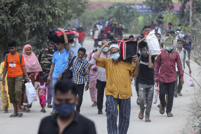 People leaving for their native places to celebrate Eid-al-Fitr arrive at the Mawa ferry terminal in Munshiganj, Bangladesh, Thursday, May 13, 2021. (AP Photo/Mahmud Hossain Opu)