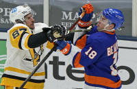 Pittsburgh Penguins center Sidney Crosby (87) uses his stick to fend off New York Islanders left wing Anthony Beauvillier (18) during the third period of an NHL hockey game, Sunday, Feb. 28, 2021, in Uniondale, N.Y. (AP Photo/Kathy Willens)