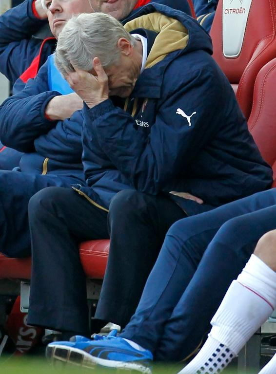 Arsenal's manager Arsene Wenger reacts in his seat as his team try to come back from two goals down in their FA Cup quarter-final match against Watford, at the Emirates Stadium in London, on March 13, 2016