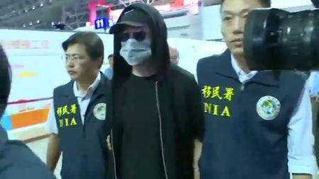 Cody Wilson, a Texan 3-D printed gun maker who flew to Taiwan as police investigated an accusation he had sex with an underage girl, is escorted by immigration officers at Taoyuan international airport, Taiwan, September 22, 2018 in this still image from video. FTV/via Reuters TV